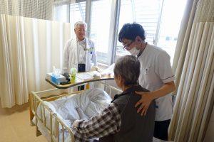 入院患者にリハビリについて説明する井上院長(左)